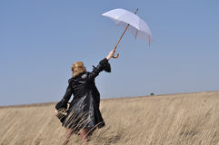 Woman with umbrella rain. Blonde is in the field and tries to keep him from wind gust, at arm's length against the sky stock photos