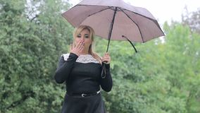 Woman with an umbrella in the rain poses to the camera in the park. Girl with an umbrella in black dress stock video footage