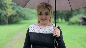 Woman with an umbrella in the rain poses to the camera in the park. Girl with an umbrella in black dress stock video