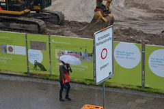 Woman with umbrella during Raining day wet street, construction project in fischerinsel Royalty Free Stock Images