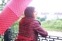 Woman with umbrella red on street tree Royalty Free Stock Image
