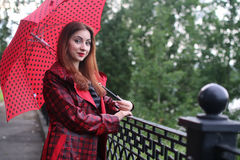 Woman with umbrella red on street tree Royalty Free Stock Photos
