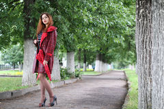 Woman with umbrella red on street tree Royalty Free Stock Images