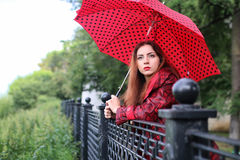 Woman with umbrella red on street tree Royalty Free Stock Photo