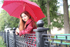 Woman with umbrella red on street tree Stock Images