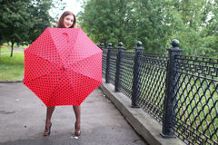 Woman with umbrella red on street tree Stock Photo