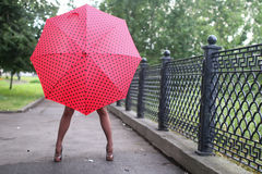 Woman with umbrella red on street tree Stock Photography