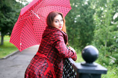 Woman with umbrella red on street tree Stock Photos