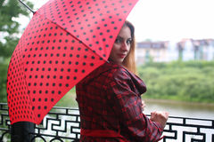 Woman with umbrella red on street tree Royalty Free Stock Photography