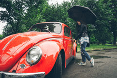Woman with umbrella sits in red retro car Royalty Free Stock Photos