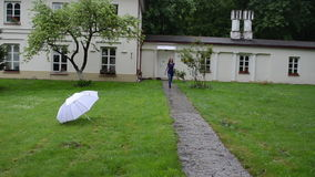 Woman umbrella smile spin. Woman walk from house and take big white umbrella on meadow grass and spin it with smile on cheerful face stock footage