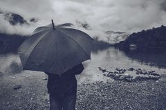 Woman with umbrella standing in the rain. And looking into distance over mountain lake. Solidtude and loneliness. Black and white image Royalty Free Stock Photography