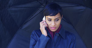 Woman with umbrella standing in rain using cell phone Royalty Free Stock Photography