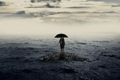 Woman with umbrella standing on the rock in the middle of the sea royalty free stock images