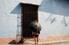Woman with umbrella in the street of Havana. A women uses an umbrella as a protection against the sun as she talks with somebody hidden from view, in the streets Royalty Free Stock Photos
