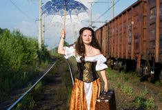 Woman with umbrella and suitcase on railway Royalty Free Stock Photography