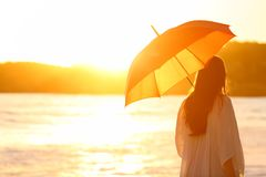Woman with umbrella at sunset on the beach. Back view portrait of a woman walking with an umbrella at sunset on the beach Stock Photography