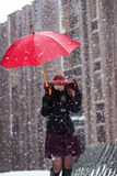 Woman with umbrella try hide from snowfall Stock Photography