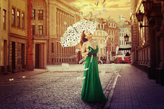 Woman with umbrella under a money rain Stock Images