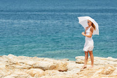 Woman with umbrella Walking on the Beach Stock Photography
