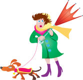 Woman with umbrella. A woman walking her small dog on a very windy day Royalty Free Stock Photos