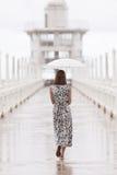 Woman and umbrella walking on jett bridge in raining day Royalty Free Stock Photography