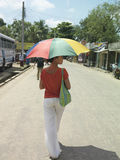 Woman With Umbrella Walking On Road Stock Images