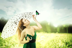 Woman with umbrella walking though a park playing with a butterfly. Beautiful woman with umbrella walking though a park playing with a butterfly royalty free stock image