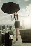 Woman with umbrella walks on rooftop Stock Photos