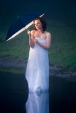 Woman with umbrella with a warm light Stock Photography