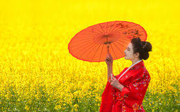 Woman with umbrella in the yellow flowering field Royalty Free Stock Image