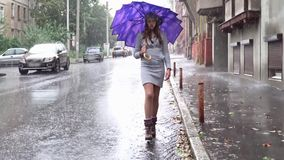 Woman with umbrella. Young beautiful girl with an umbrella goes through the puddles in the rain on the city street stock video footage