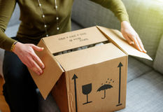 Woman unboxing good cardboard box stock image