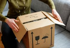 Woman unboxing good cardboard box. Woman unpacking unboxing cardboard carton box with protective foam pads inside after buying ordering online via internet a Stock Photography