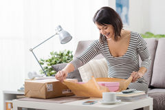 Woman unboxing a parcel. Happy excited woman at home, she has received a postal parcel and she is unboxing her gift, delivery and online shopping concept royalty free stock image