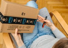 Woman unboxing unpacking amazon box. PARIS, FRANCE - NOV 4, 2017: Woman unpacking on the living room armchair the Amazon Prime large cardboard box with Prime royalty free stock images