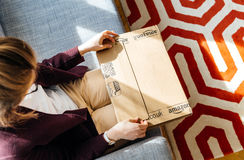 Woman unboxing unpacking Amazon.com box. PARIS, FRANCE - APR 24 2017: Living room view from above of woman unpacking unboxing Amazon cardboard box with logotype royalty free stock photo