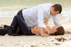 Woman is unbuttoning shirt on man as they lay on t. A beautiful young couple on the beach in wet clothes, the woman is laying on her back, the man is over her Royalty Free Stock Images