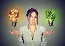 Woman uncertain diet choice junk food or vegetables light bulb Stock Images