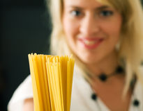 Woman with uncooked spaghetti Royalty Free Stock Photo