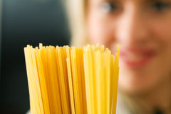 Woman with uncooked spaghetti Royalty Free Stock Photos