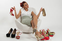 Woman undecided about which shoes to wear. Beautiful Italian woman undecided about which shoes to wear Stock Images