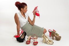 Woman undecided about which shoes to wear Royalty Free Stock Image