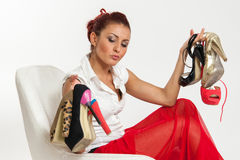 Woman undecided about which shoes to wear. Woman sitting on a chair undecided about which shoes to wear Stock Images