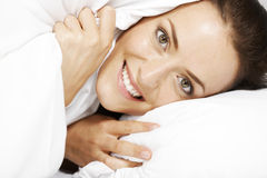 Woman under bed sheets Royalty Free Stock Photography