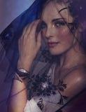 Woman under black veil. Portrait of romantic beautiful woman wearing black veil and wings bracelet on purple background Stock Photo