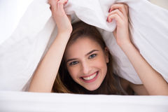 Woman under the blanket in the bed Stock Photos