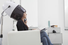 Woman Under Hooded Dryer Machine In Hair Salon. Side view of young women under hooded dryer machine in hair salon stock photography