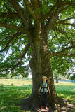 Woman under a huge oak tree Stock Images