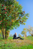Woman under mountain ash tree Royalty Free Stock Image
